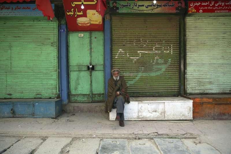 阿富汗首都喀布爾,一名老者坐在因疫情關閉的店舖前(美聯社)