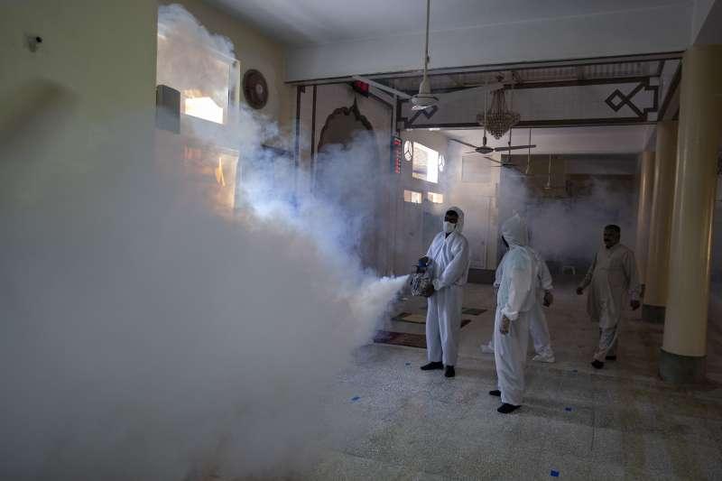 齋戒月即將到來,疫情當前,巴基斯坦拉瓦平第市的志工正在一間清真寺消毒(美聯社)