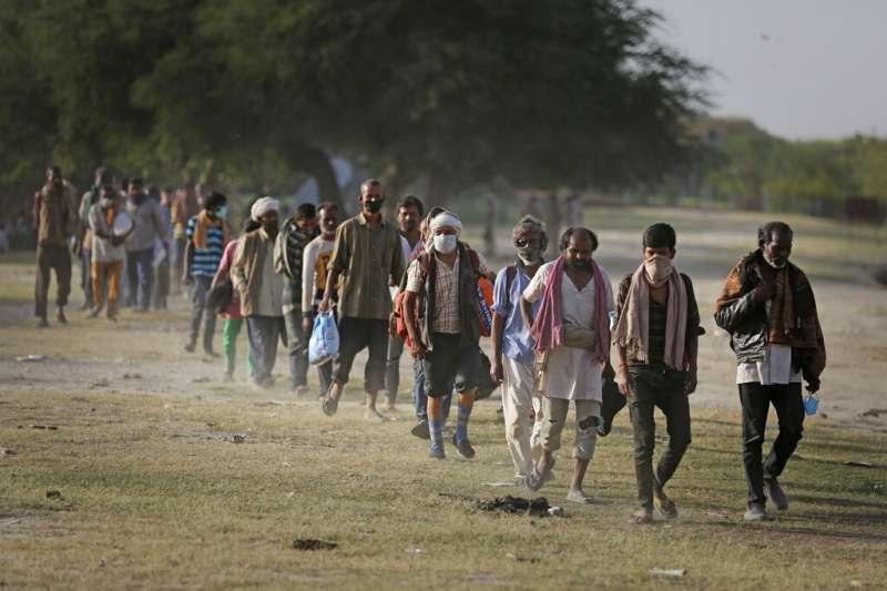 武漢肺炎疫情衝擊印度,當局實施全國封鎖措施,窮人大受衝擊。圖為返家路上的各地工人。(AP)