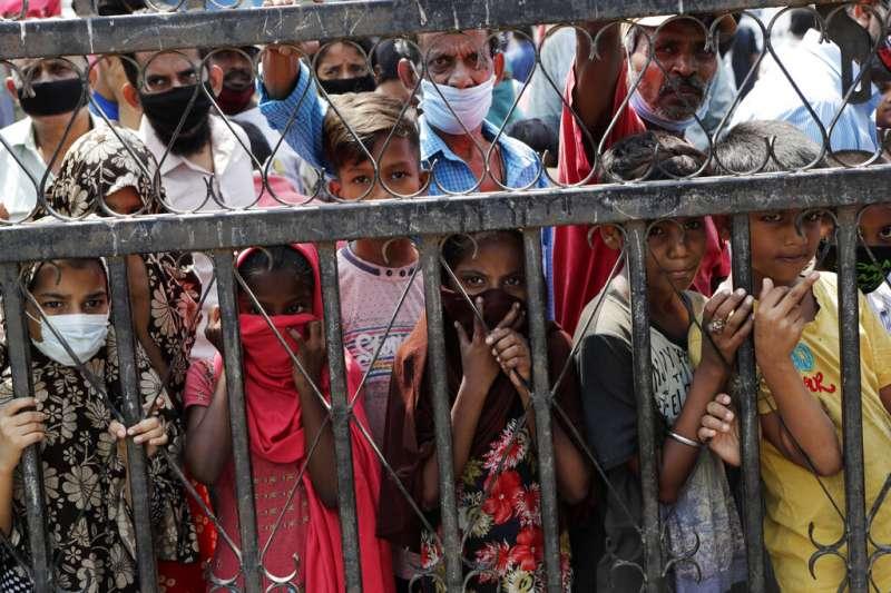 新冠肺炎(武漢肺炎)疫情衝擊印度,實施全國封鎖措施,窮人大受衝擊。圖為等待領取糧食補給的人們。(AP)