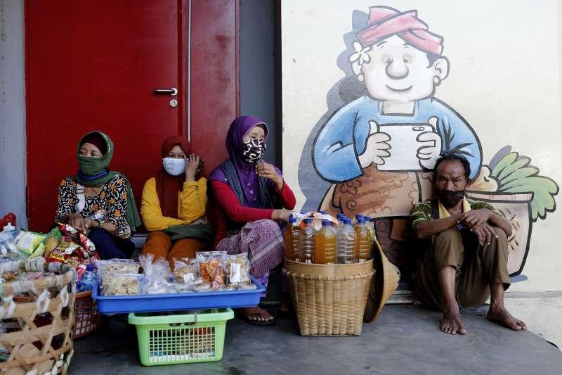 印尼的武漢肺炎疫情延燒,峇里島街頭小販戴著口罩自保(美聯社)