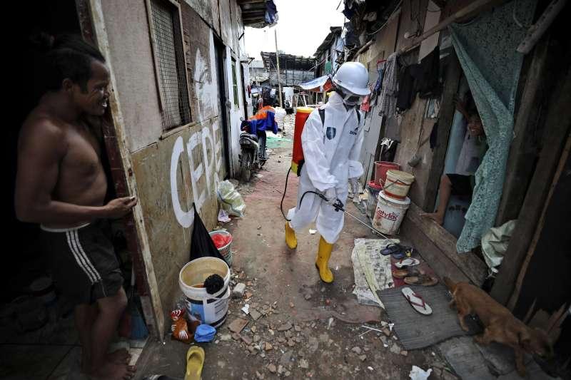 印尼的武漢肺炎疫情延燒,一名工作人員正在首都雅加達的貧民窟消毒(美聯社)