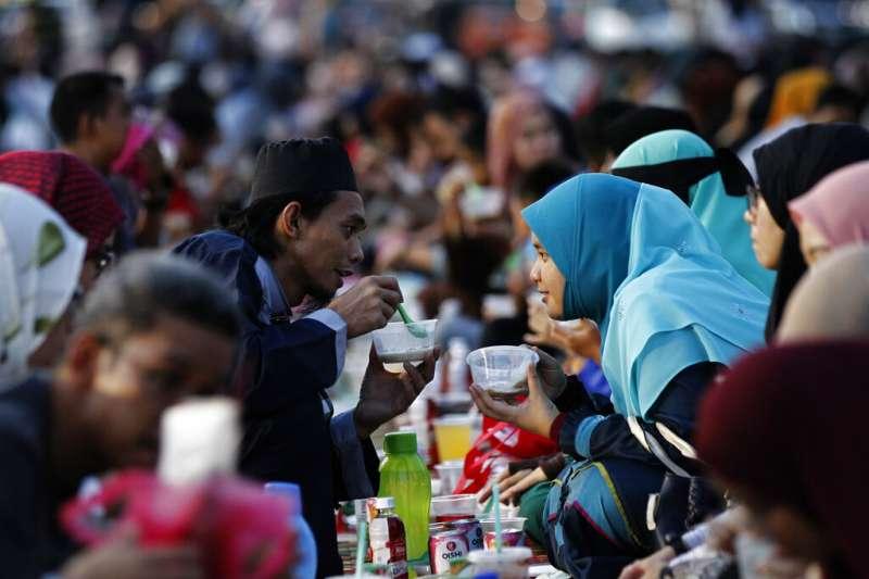 一對馬來西亞的穆斯林夫婦在伊斯蘭教齋月一起享用開齋飯。(美聯社)