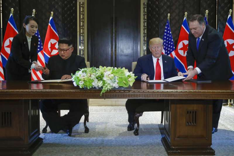 川普與金正恩在新加坡川金會期間簽署文件,龐畢歐與金與正則在一旁協助。(美聯社)
