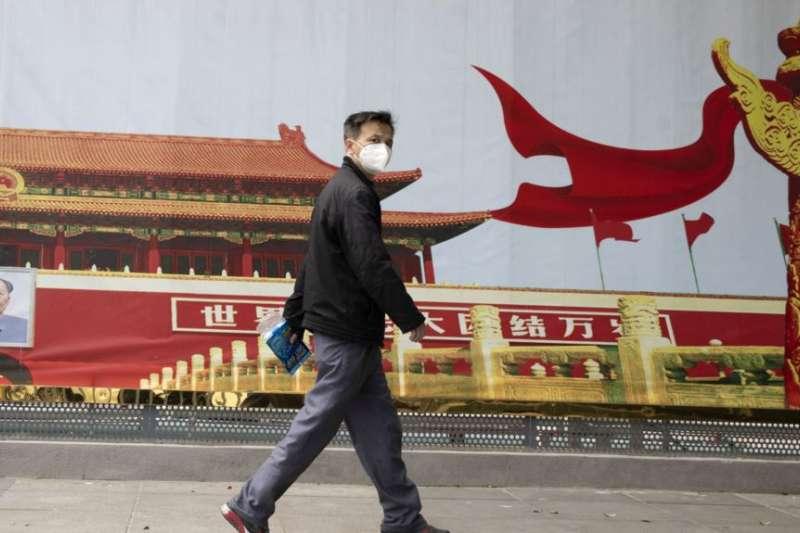 湖北武漢一名居民走過街頭一幅北京天安門的招貼畫。(美聯社)