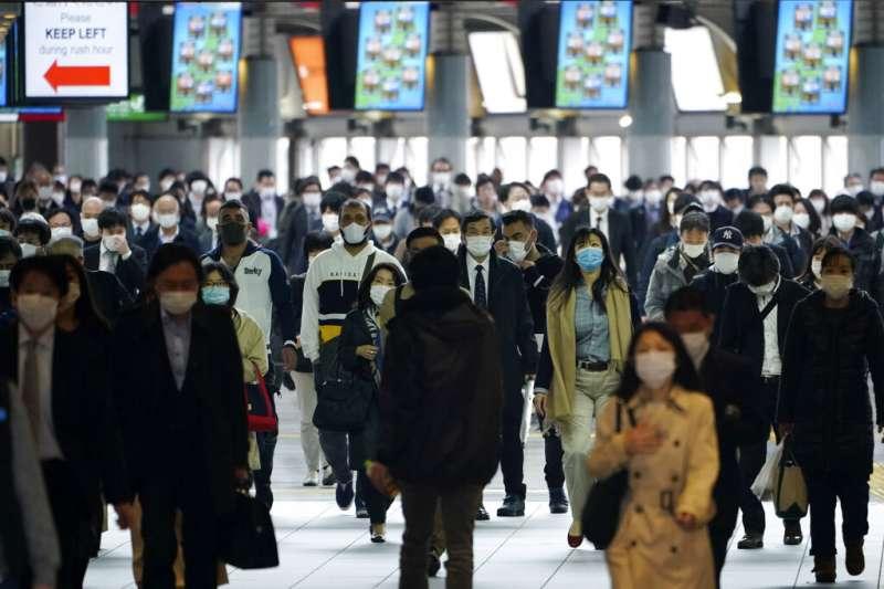 雖然安倍晉三呼籲民眾盡量在家辦公,東京地鐵站裡的上班族依舊趕著通勤。(美聯社)