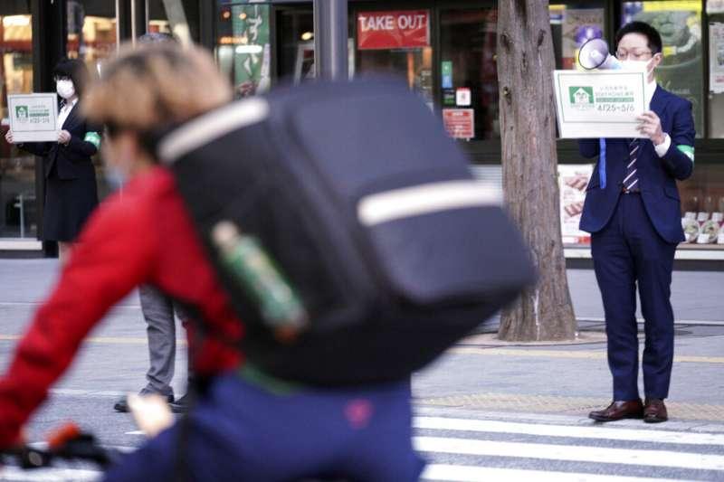 東京都政府的職員在街上呼籲民眾待在家裡,不要外出。(美聯社)