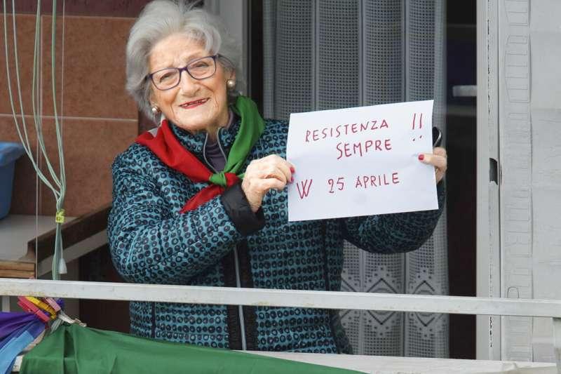 新冠疫情讓義大利解放75週年的紀念活動停辦,但當年反墨索里尼的游擊隊成員依舊在自家陽台慶祝這個重要的日子。93歲的Teresa Vergalli舉著手寫標語「抵抗到底,4月25日萬歲!」(美聯社)