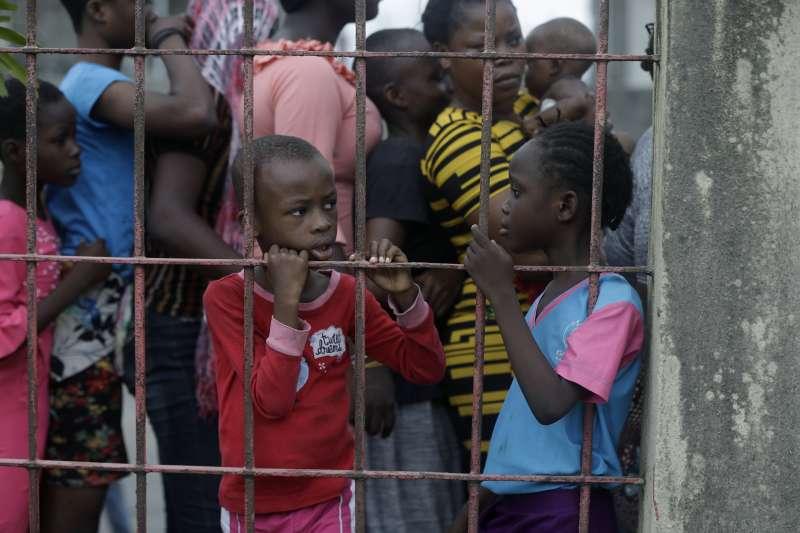 新冠肺炎侵襲奈及利亞,圖為當地兒童排隊等候領取捐贈糧食。(AP)
