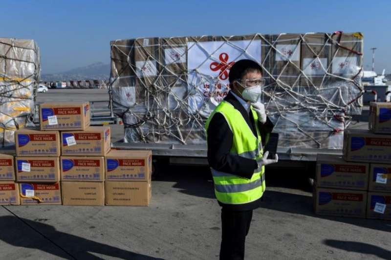 希臘雅典國際機場的一名工人站在從中國運抵的口罩等抗疫防護用品。(美國之音)