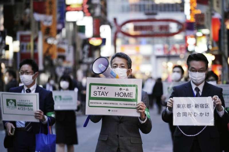 新冠肺炎肆虐全球。圖為日本東京都官員呼籲民眾在家自肅,避免新冠肺炎疫情擴大。(AP)
