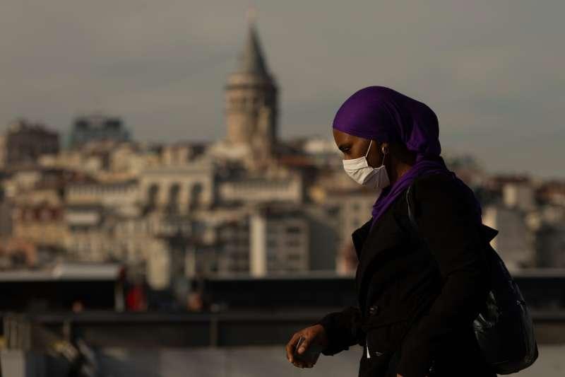 武漢肺炎(新冠肺炎)疫情在土耳其肆虐,伊斯坦堡一名女性行人戴著口罩自保,背景是知名的加拉達塔。(資料照,美聯社)