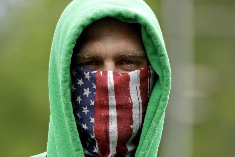 美國各州的禁足令逐漸鬆綁,民眾戴著口罩上街(AP)