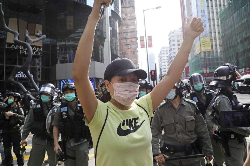 2020年4月,香港壟罩在新冠肺炎疫情中,警察與示威者都戴著口罩。(AP)