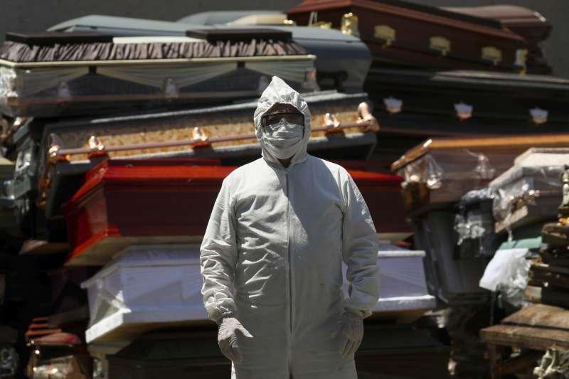 墨西哥一處火葬場的工作人員,站在新冠肺炎死者的成堆棺木旁。在新冠病毒疫苗出現前,人們必須適應疫情下的新日常(AP)