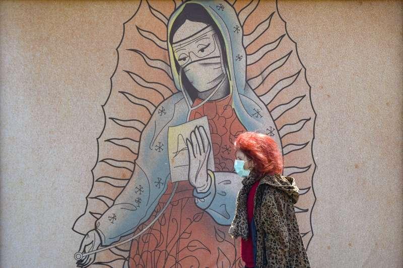 羅馬尼亞首都布加勒斯特,一名戴口罩的婦女行經以天主教「瓜達露佩聖母」為原型的醫療人員畫像前(美聯社)