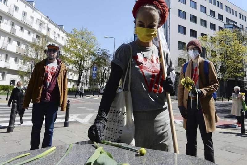 4月19日,波蘭首都華沙,戴著口罩的民眾以黃水仙紀念華沙猶太區起義(美聯社)