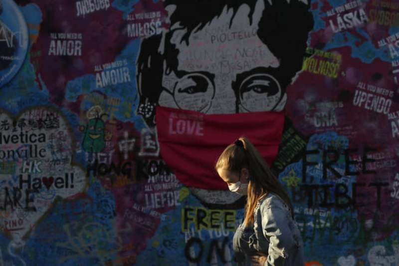 4月6日,捷克布拉格,一名戴著口罩的女子行經藍儂牆(美聯社)