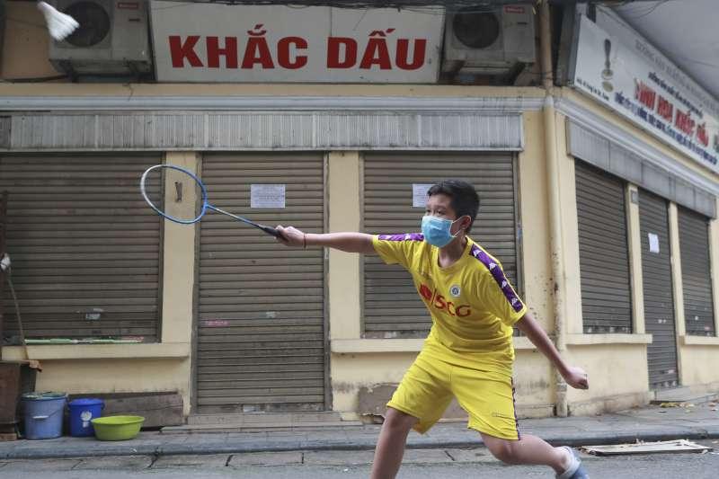 4月22日,越南河內,一名戴著口罩的小男孩在街上打羽毛球(美聯社)