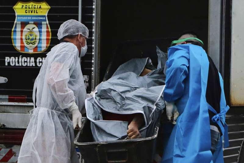 巴西的醫護人員正在將確診死亡的患者遺體送上車。(美聯社)
