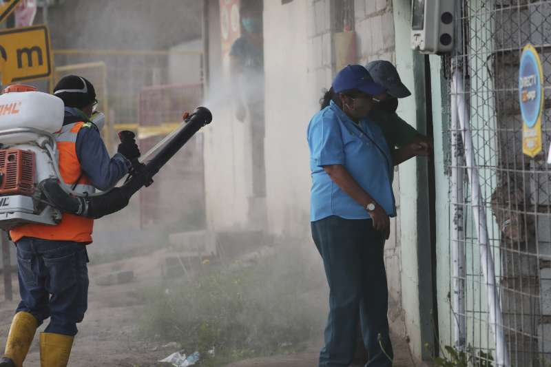 厄瓜多新冠肺炎疫情嚴重,婦人因新冠肺炎死在家中,圖為公衛人員前往社區消毒。(AP)