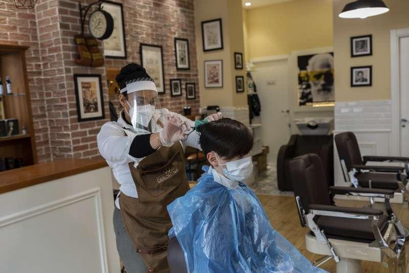 武漢肺炎:各國逐步解除封城,圖為西班牙民眾理髮也戴口罩(AP)