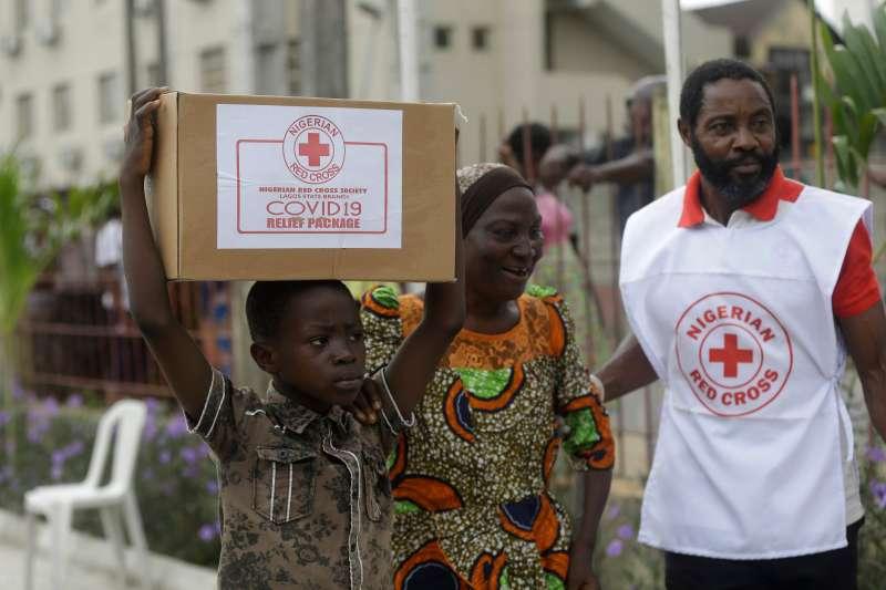 奈及利亞第一大城拉各斯,來自貧民窟的母子領到當地紅十字會分送的免費食物(美聯社)