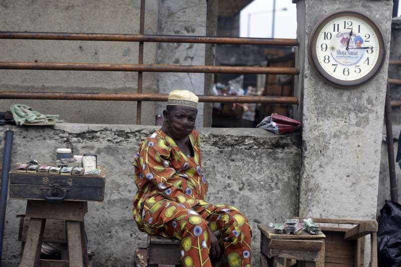 奈及利亞的武漢肺炎疫情嚴峻,第一大城拉各斯街頭的鐘錶匠戴著口罩工作(美聯社)