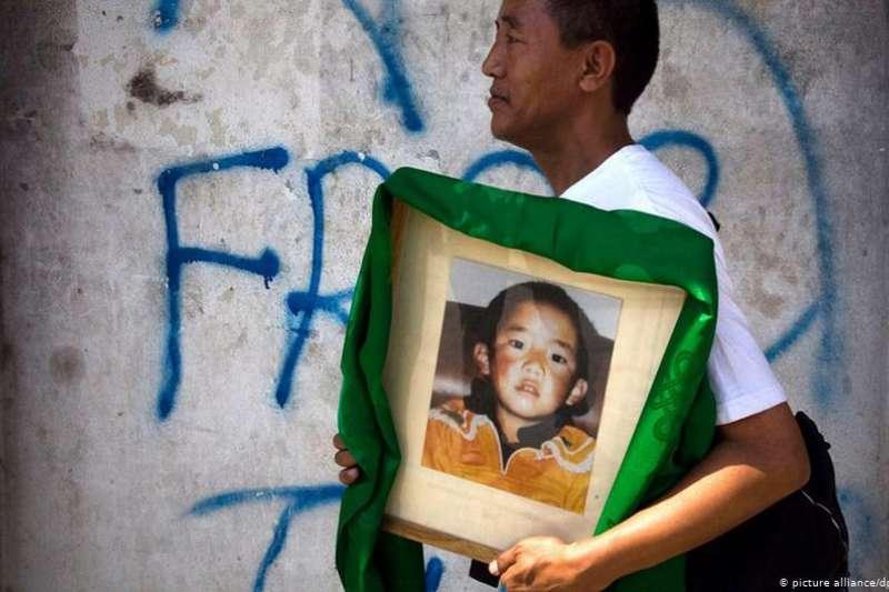 2012年,一名流亡藏人在尼泊爾首都加德滿都街頭手持根敦確吉尼瑪畫像。(德國之聲)