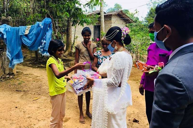 4月27日,斯里蘭卡的達沙那與帕瓦妮在登記結婚後,穿著禮服分送物資與禮物給當地的窮苦民眾(美聯社)