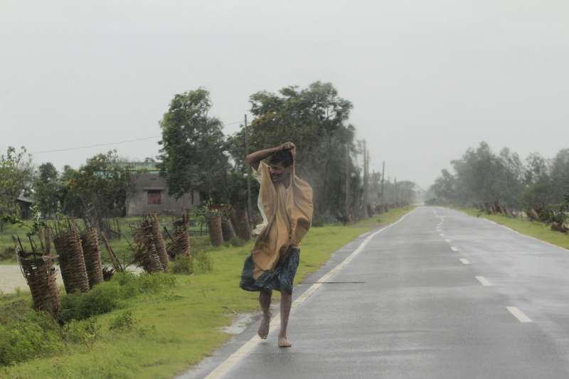 颶風「安攀」20日在印度與孟加拉登陸,印度奧里薩邦一位民眾冒雨行進(美聯社)