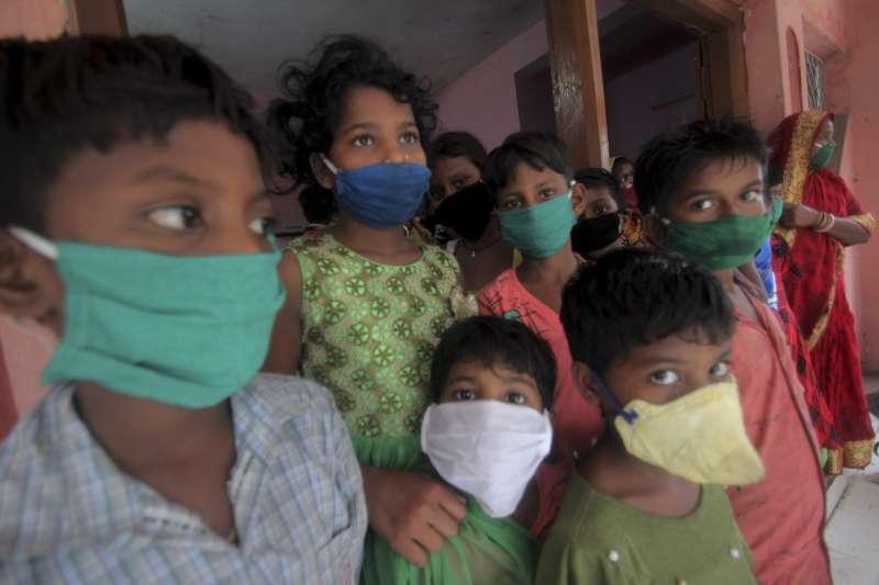 颶風「安攀」20日在印度與孟加拉登陸,印度奧里薩邦避難所裡的孩童被要求戴上口罩(美聯社)