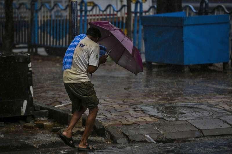颶風「安攀」20日在印度與孟加拉登陸,印度西孟加拉首府加爾各答一名民眾頂著風雨前進(美聯社)