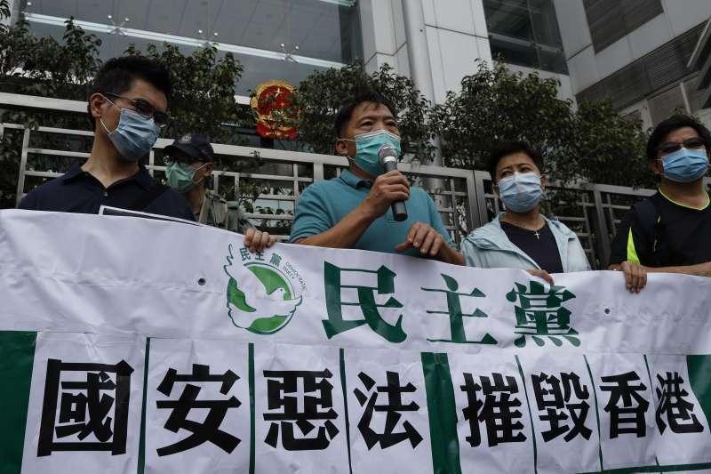 中國授權人大常委制定「港版國安法」,香港民主黨人士到中聯辦前拉布條抗議。(AP)