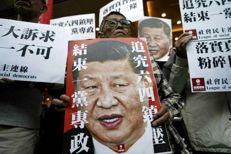 香港民主人士在街頭高舉反習近平海報,呼籲「追求六四鎮壓、結束一黨專政」。(美聯社)