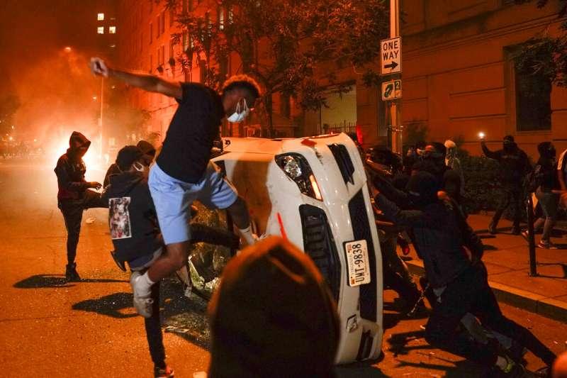 為佛洛伊德之死走上街頭的美國民眾,在華府白宮附近推翻車輛。(美聯社)