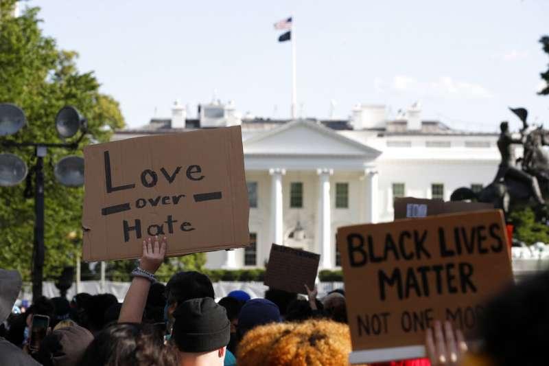 為佛洛伊德之死走上街頭的美國民眾,在白宮前高舉「愛戰勝恨」、「黑人的命也是命」等抗議標語。(美聯社)