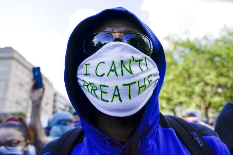 為佛洛伊德之死走上街頭的美國民眾,在白宮附近戴上寫了「我不能呼吸」(佛洛伊德遺言)的口罩。(美聯社)
