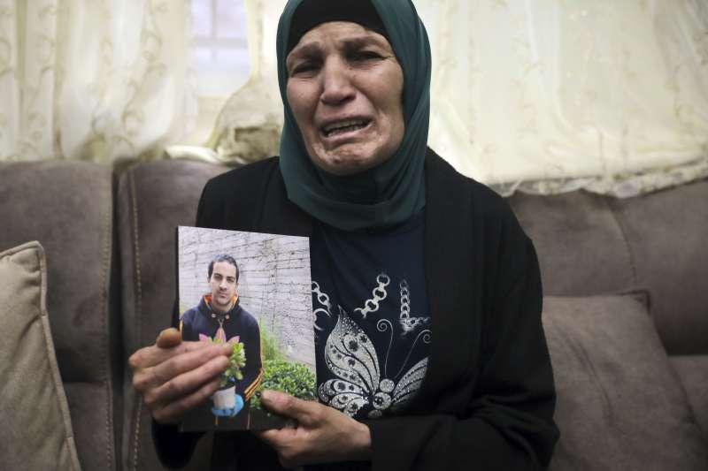 哈拉克的母親莉娜心碎拿著兒子的照片(美聯社)