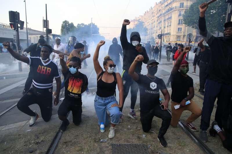 美國反種族歧視示威潮延燒,法國也掀起示威。圖為法國民眾模仿美國運動員單膝跪地的抗議姿勢。(AP)