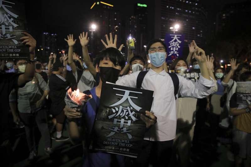 香港民眾在維多利亞公園悼念六四受難者,並且高舉「五大訴求缺一不可」的手勢、以及「天滅中共」的標語。(美聯社)