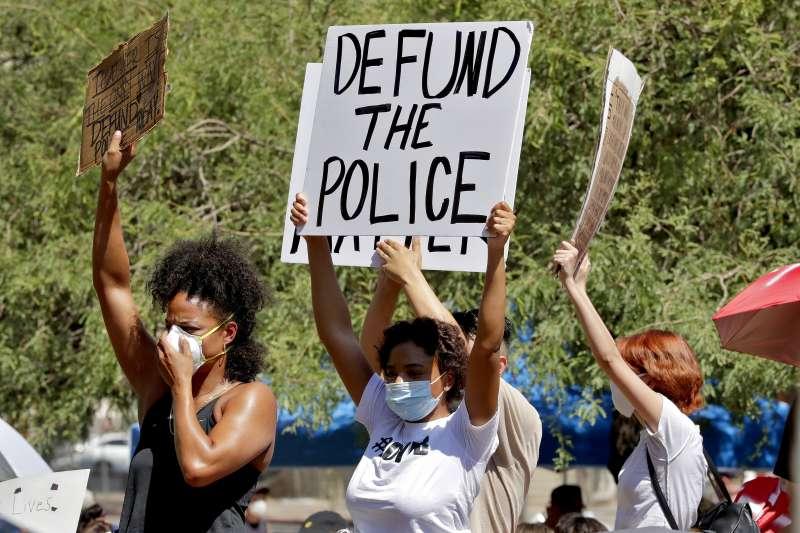 美國的反種族歧視示威運動越演越烈,示威群眾高舉「撤銷警局經費」(defund the police)標語。(資料照,美聯社)