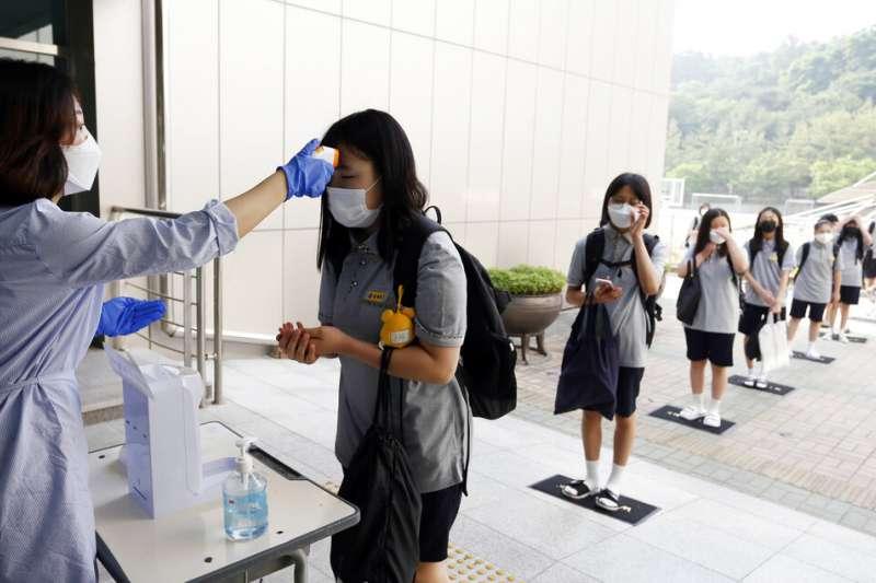 南韓忠州一所中學的學生戴著口罩,在進入教室前進行體溫測量,而且彼此也注意保持社交距離。(美聯社)