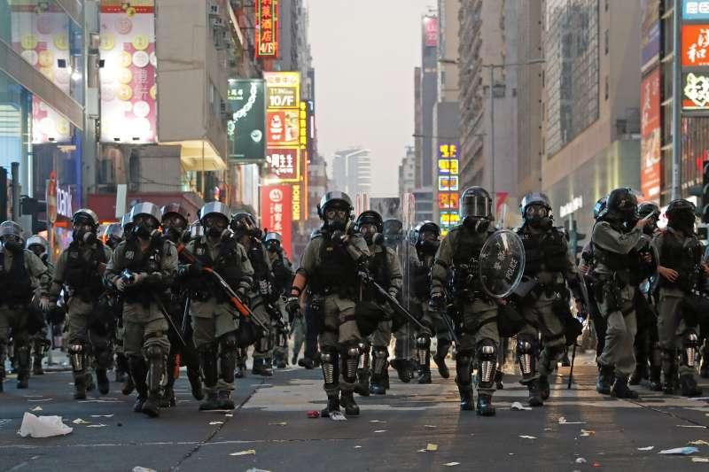香港反送中抗爭一週年:2019年10月1日,防暴警察上街掃蕩堵路的示威者。(AP)