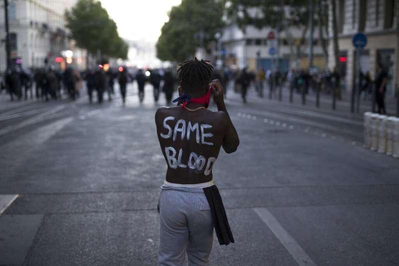 數以萬計的法國民眾走上街頭,抗議種族歧視與警察暴力。一位示威者在背後寫著「相同的血」。(美聯社)