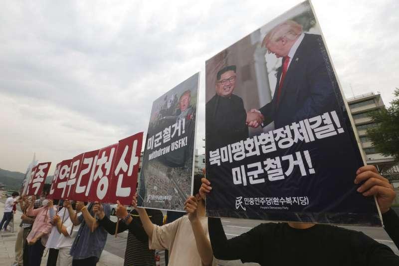 南韓示威者高舉川普與金正恩的合照,下方則用韓文寫著「美軍撤退!」,譴責美韓政府的北韓政策根本沒有效果。 (美聯社)