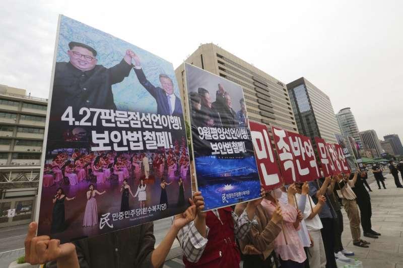南韓民眾在美國駐韓大使館外高舉文在寅與金正恩的合照,對美韓政府的北韓政策大表不滿,照片下方則用韓文寫著「4月27日停止執行國家安全法、並執行板門店宣言」。 (美聯社)