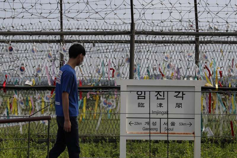 一名遊客在南北韓交界附近的臨津閣遊覽。隨處可見的彩帶上寫著「希望兩韓統一」,立牌上寫的是當地與開城(北韓大城)及首爾(南韓首都)的距離。 (美聯社)