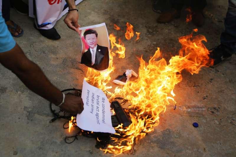 2020年6月16日,一名印度男子在艾哈邁達巴德舉行的抗議活動中,焚燒中國國家主席習近平的照片。據報當天至少有三名印度軍人在與中國的衝突中喪生。(美聯社)
