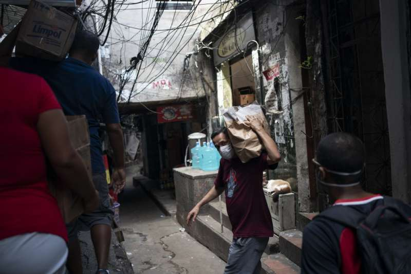 巴西里約熱內盧志工在當地最大貧民窟羅西尼亞分送肥皂與清潔劑,希望防堵武漢肺炎疫情擴散(美聯社)